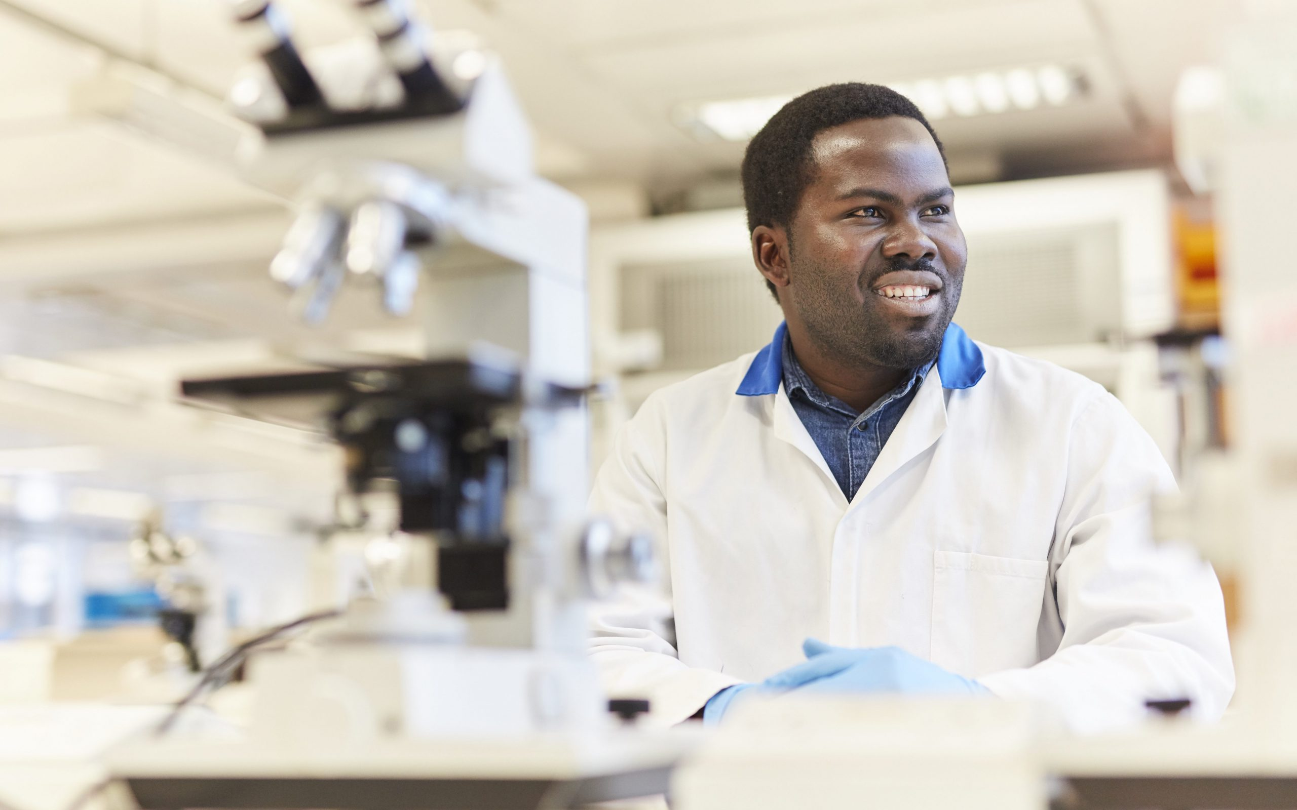A picture of a young man wearing a lab coat in a science lab with a microscope in the forefront.