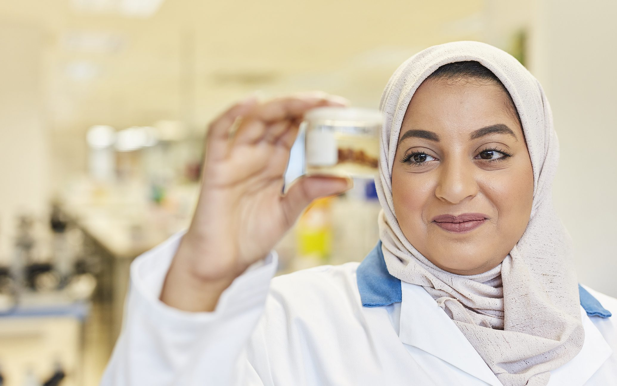 An image of a female scientist wearing a headscarf and holding a scientific sample in a pot