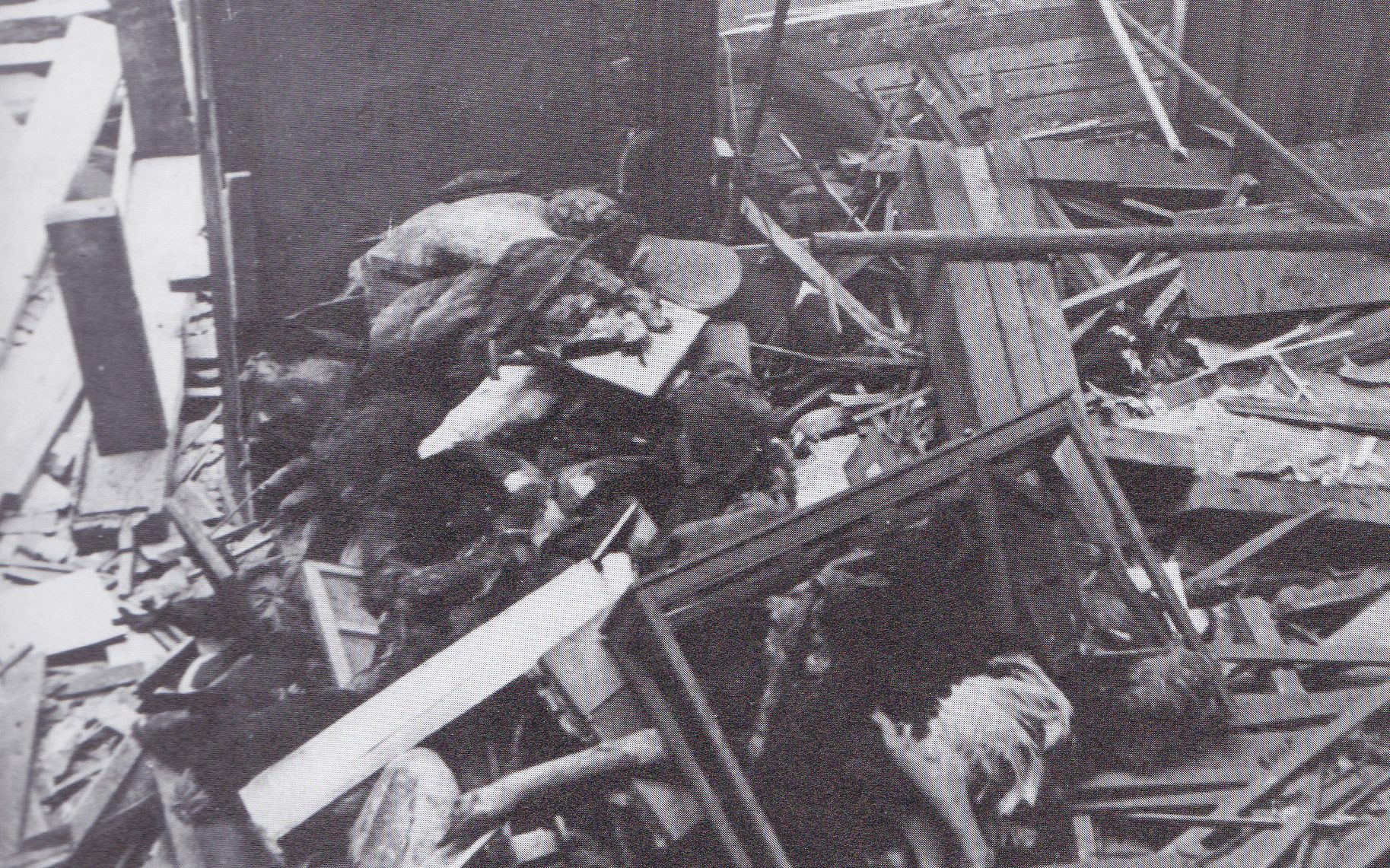 A black and white photograph showing damage and debris piled on the floor.