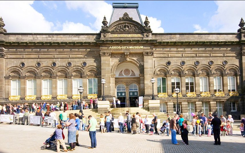 A photograph of the Leeds City Museum with crowds outside and a blue sky.