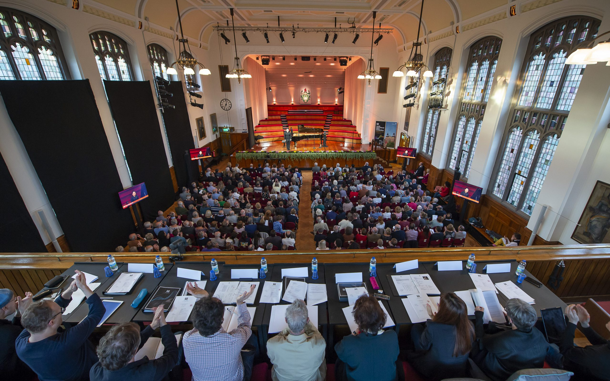 Picture looking down into the great hall, showing judges, audience and grand piano on stage.