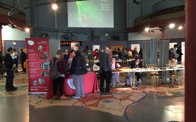 A picture of the Leeds Science fair showing people gathered around exhibition stands.